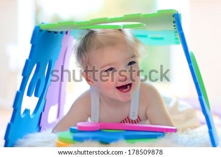 Funny little toddler girl playing hide and seek and learning numbers with colorful soft puzzles - stock photo