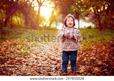 Funny Little 2 year old Kid Laughing and Walking in the Park at the Sunset with Toy in His Hand. Happy Childhood Concept. Image toned with Bright Instagram Colors. Space for Text. - stock photo