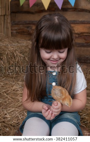 funny lovely baby girl little child in trendy in a jeans dress with chickens and ducklings. Easter holiday concept: nest with baby chick. little girl playing with a chicken on a fabulous farm
