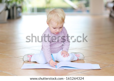 Funny lovely baby girl plays indoors drawing with colorful pencils sitting on tiles floor - stock photo