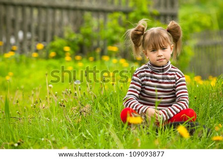 Funny lovely little five-year girl sitting in grass