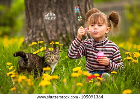 Funny lovely little girl and a cat, blowing soap bubbles