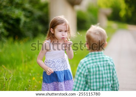 Funny lovely little girl and her brother blowing soap bubbles  - stock photo