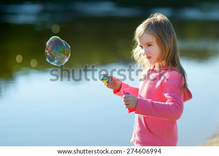 Funny lovely little girl blowing soap bubbles on sunset outdoors - stock photo