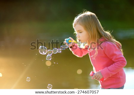 Funny lovely little girl blowing soap bubbles on sunset outdoors
