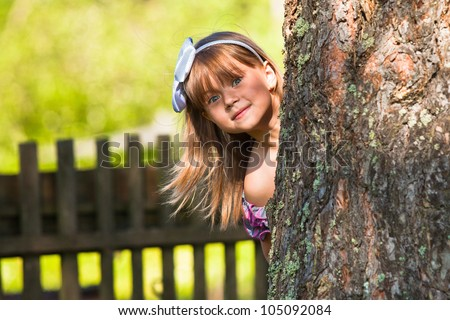 Funny lovely little girl playing in the park - stock photo
