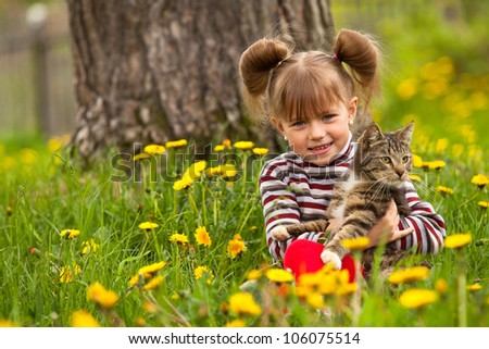 Funny lovely little girl playing with a cat in the park