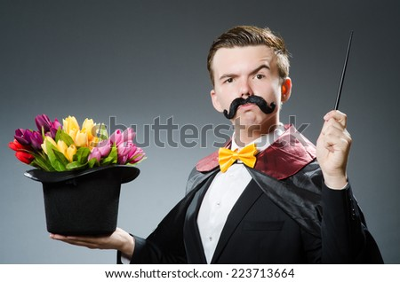 Funny magician with wand and hat - stock photo