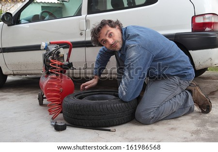 funny man and car spare tire - stock photo
