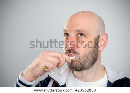 funny man brushing teeth in front of gray background