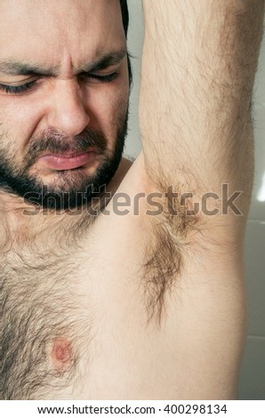 funny man having bad smell from armpit - stock photo