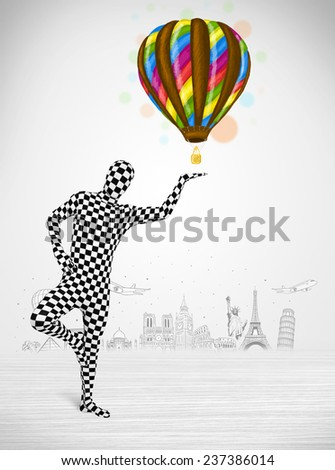Funny man in full body suit holding colorful balloon, tourist attractions in background - stock photo