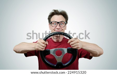 Funny man in glasses with a steering wheel, car drive concept  - stock photo
