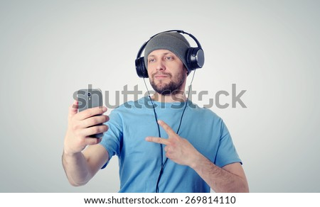 Funny man in hat and headphones photographing himself on a smartphone - stock photo