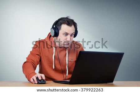 Funny man in headphones with laptop. Game-play