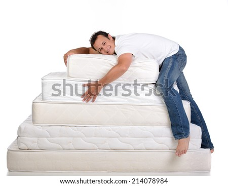 Funny man in pajamas sitting on lots of mattresses, isolated on white background - stock photo