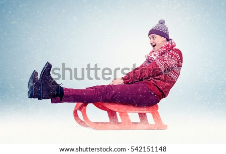 Funny man in red sweater and cap on sled in the snow, concept winter fun