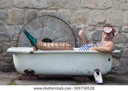 Funny man in retro swimwear with snorkeling gear lying in the bathtub outdoor. Diver in vintage style swimsuit with diving goggles and bathing cap gesturing thumb up from tub. Home holidays. - stock photo