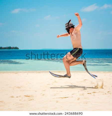 Funny man jumping in flippers and mask. Holiday vacation on a tropical beach at Maldives Islands. - stock photo