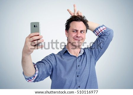 Funny man photographing himself on a smartphone. Be fashionable concept