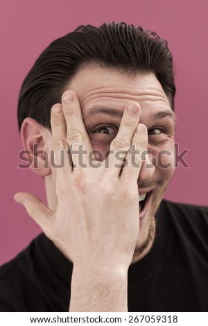 Funny man portrait hiding behind his hand