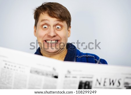 Funny man reading a newspaper. Shocked bad news.