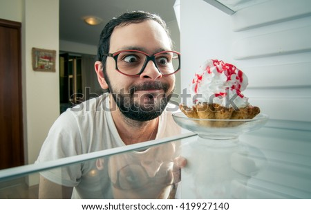funny man sees the sweet cake in the fridge - stock photo
