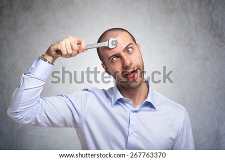 Funny man using a wrench to fix his brain - stock photo
