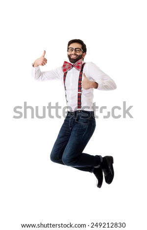 Funny man wearing suspenders jumping with thumbs up. - stock photo
