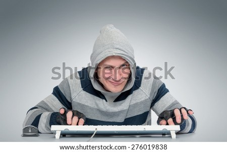 Funny man with a keyboard in front of computer on background - stock photo
