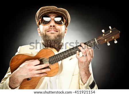 funny man with glasses play guitar ukelele on black background