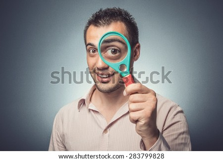 Funny man with magnifier looking, big eye, dark gray background. Studio shot