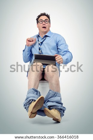 Funny man with tablet pc sitting on the toilet. - stock photo