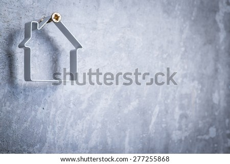 Funny metal house hanging on the screw in the grey concrete wall - stock photo