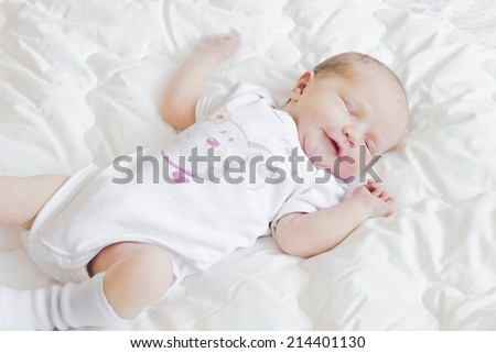 funny mischievous baby lies at the crib and smiling - stock photo