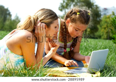 Funny mom and daughter with modern laptop outdoors - stock photo