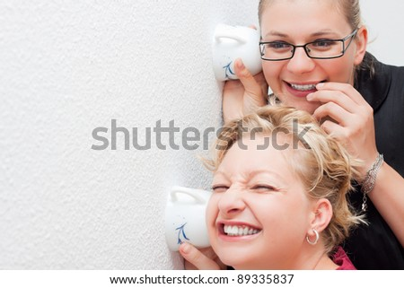 Funny moment of two young women spying. - stock photo