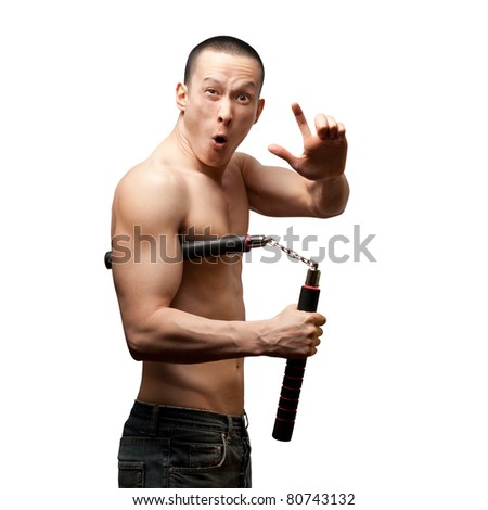 funny muscular shaolin monk with nunchaku in his hands - stock photo