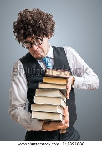 Funny nerd man holds many books in hands. - stock photo