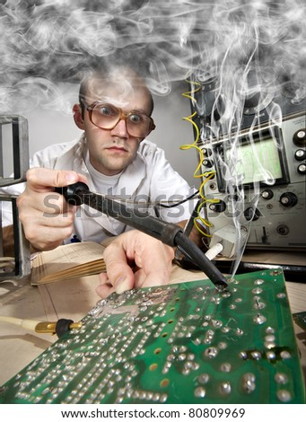 Funny nerd scientist soldering at vintage technological laboratory - stock photo