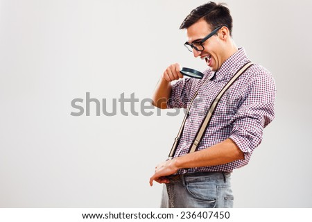 Funny nerdy guy is peeking in his paints with loupe ,his macho problems are seems to be over.Wait,wait...I think I see some changes! - stock photo