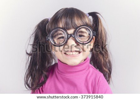 Funny nerdy little girl smiling. Toned image with shallow depth of field - stock photo