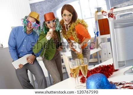 Funny new year eve party in office, businesspeople singing dancing with office tools, wearing festive party hat and glasses. - stock photo