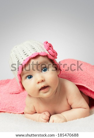 Funny newborn little baby wearing a hat with towel  - stock photo