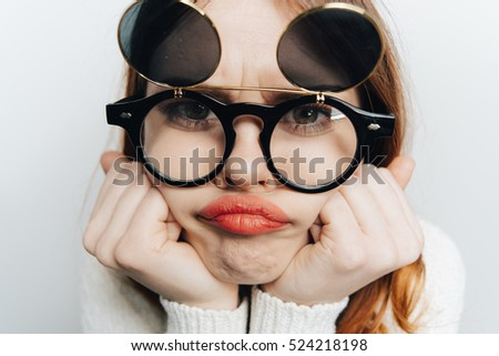 Funny offended woman looking into the camera in a funny glasses. Isolated background