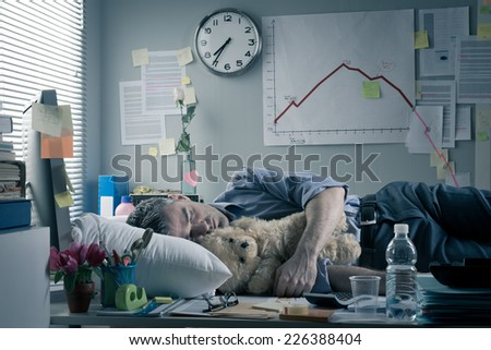Funny office worker sleeping in the office overnight with teddy bear. - stock photo