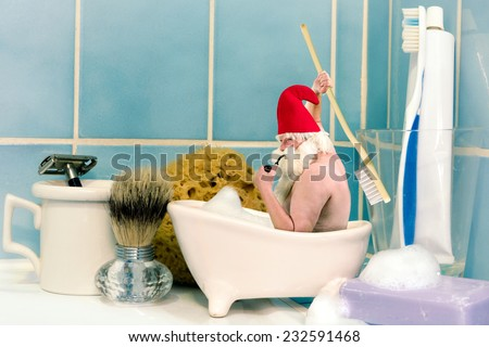 Funny old gnome taking a bath in a soap dish - stock photo