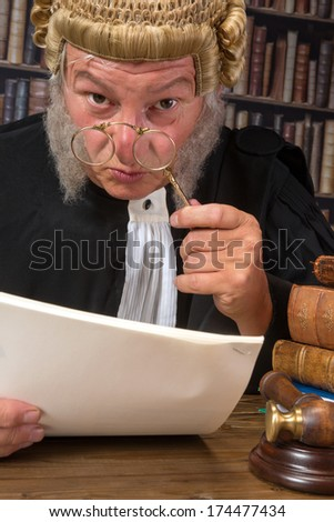 Funny old judge looking through a lorgnette - stock photo
