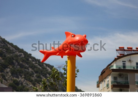 Funny orange shark with snow-white smile in the sun against the sky - stock photo