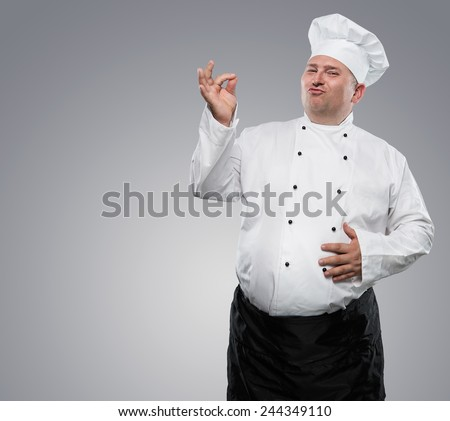 Funny overweight chef showing ok isolated on gray background with copy space - stock photo